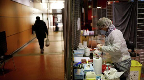 Медицинский работник в защитном костюме в центре тестирования на коронавирус во Франции