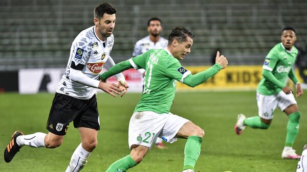 Saint-Etienne's French forward Romain Hamouma (R) fights for the ball with Angers' French midfielder Thomas Mangani (L) during the French L1 football match between AS Saint-Etienne and SCO Angers at the Geoffroy Guichard stadium in Saint-Etienne, central France, on December 11, 2020. (Photo by PHILIPPE DESMAZES / AFP)