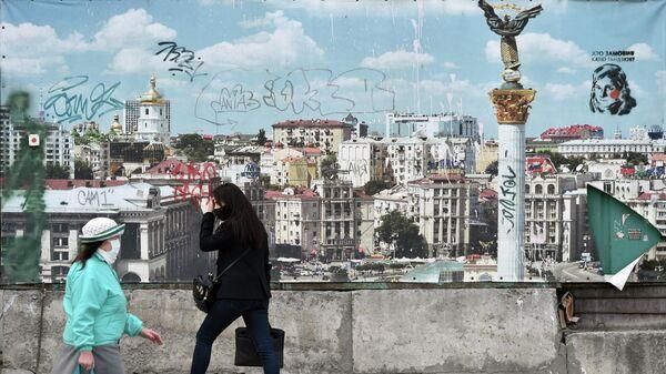 Женщины в масках проходят мимо баннера с изображением Киева