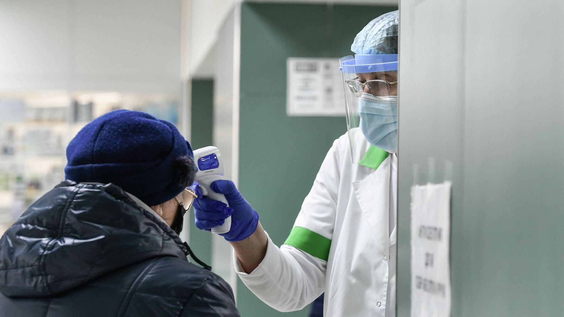 Медицинский работник проверяет температуру у пожилой женщины - РИА Новости, 1920, 13.01.2021