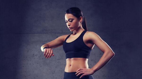 Девушка проверяет пульс на фитнес-браслете