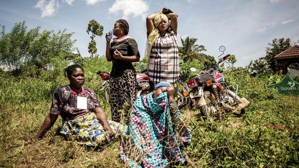 Женщины оплакивают кончину члена семьи во время похорон на окраине города Бени, провинция Северное Киву