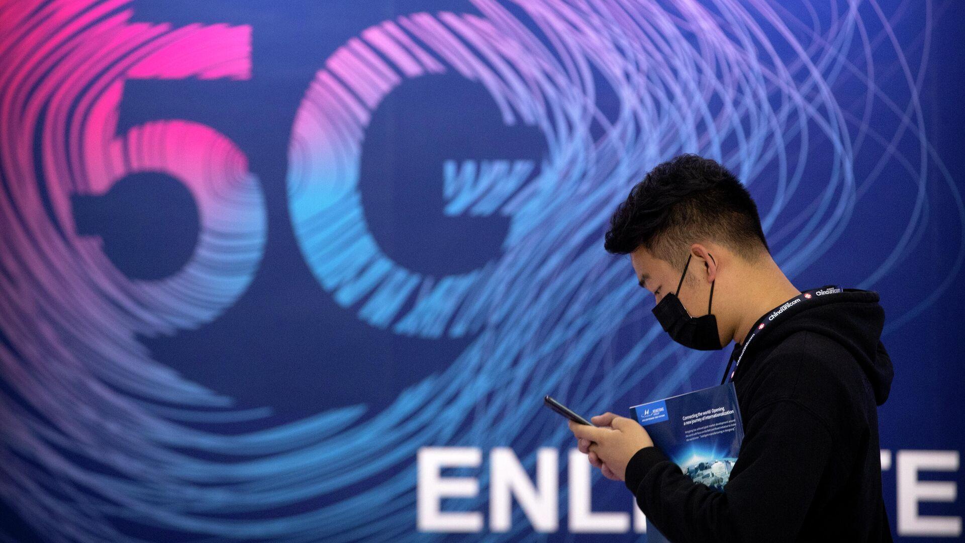Мужчина проходит мимо вывески рекламирующей связь 5G  - РИА Новости, 1920, 23.12.2020