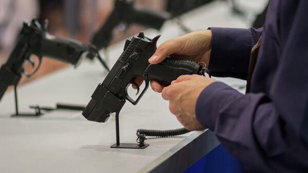 Мужчина держит в руке пистолет