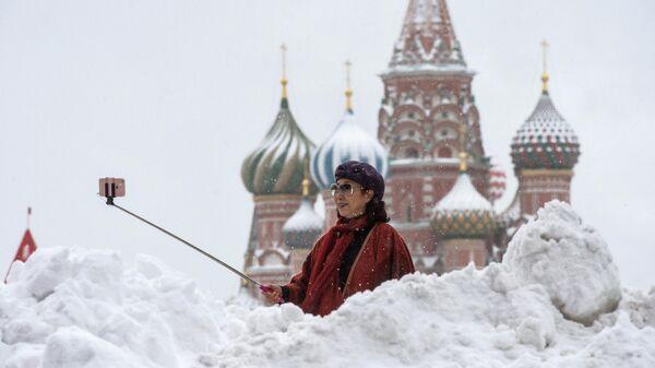 Женщина фотографируется у храма Василия Блаженного на Красной площади