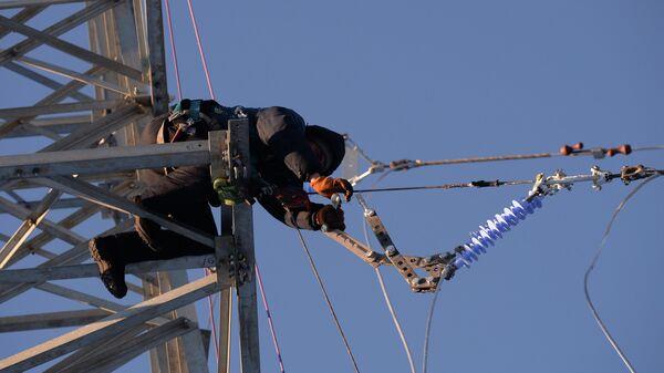 Рабочий компании Красэлектрострой монтирует высоковольтную линию электропередач