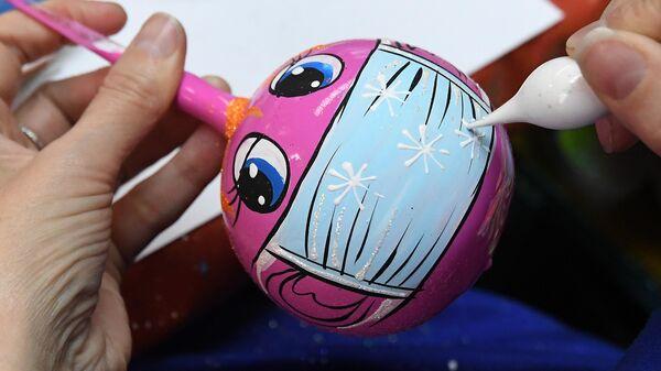 Художница расписывает стеклянный новогодний шар на фабрике игрушек Бирюсинка в Красноярске