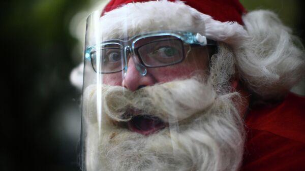 Санта-Клаус в защитной маске на улице в Мехико, Мексика