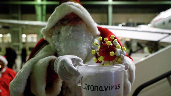 Санта-Клаус с игрушечной моделью коронавируса  в Берлине, Германия