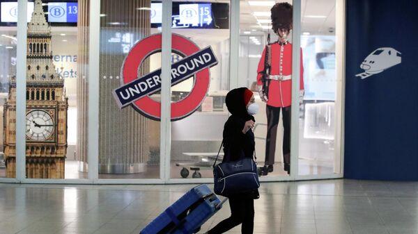 Женщина проходит мимо закрытого входа в терминал Eurostar