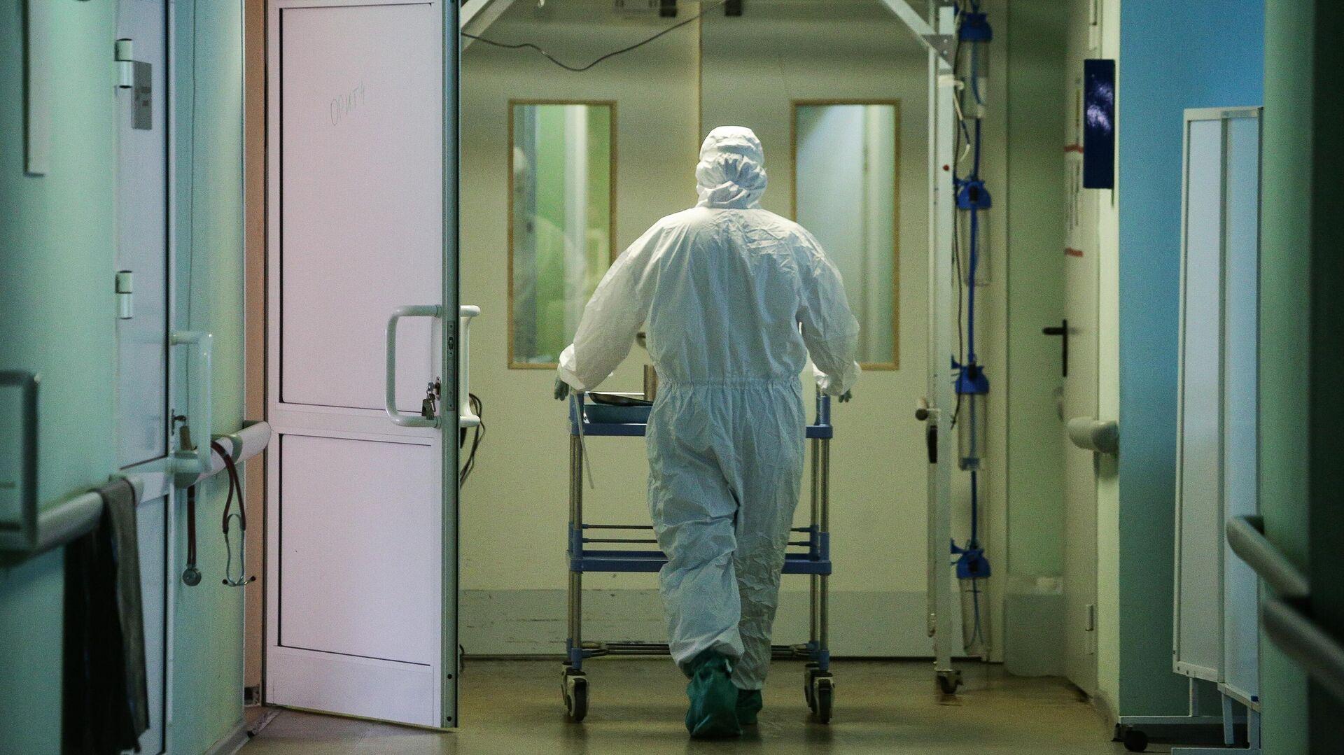 Медик в защитном противоэпидемическом костюме в коридоре Новосибирской областной клинической больницы - РИА Новости, 1920, 18.01.2021