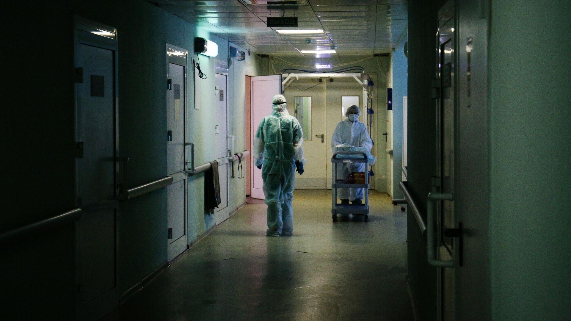 Медики в защитном противоэпидемическом костюме в коридоре Новосибирской областной клинической больницы - РИА Новости, 1920, 07.02.2021