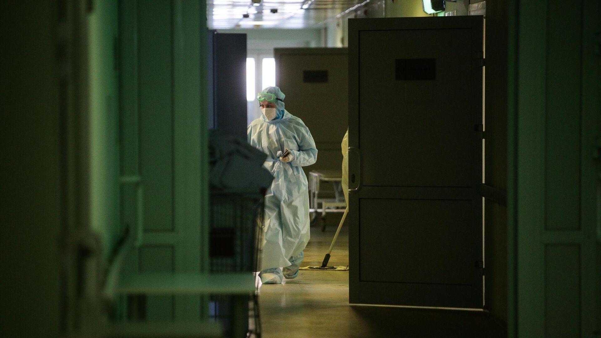 Медик в защитном противоэпидемическом костюме идет по коридору Новосибирской областной клинической больницы - РИА Новости, 1920, 27.02.2021