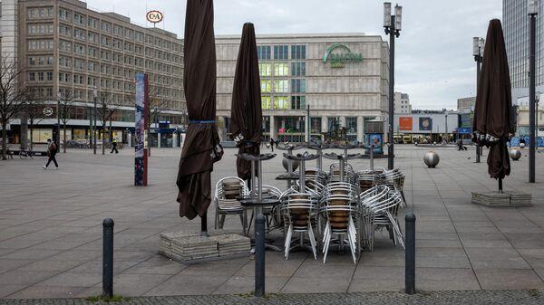 Столы и стулья возле закрытого кафе на площади Александерплац в Берлине