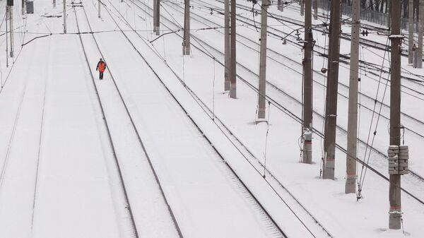 Работник железной дороги обходит железнодорожные пути