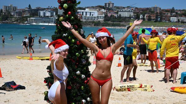 Девушки фотографируются у рождественской ели, установленной на пляже в Сиднее, Австралия