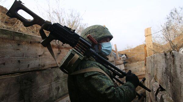 Военнослужащий Народной милиции ДНР в окопе в Новоазовском районе у села Саханка вблизи линии соприкосновени