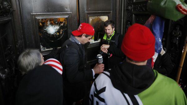 Участники акции протеста сторонников действующего президента США Дональда Трампа у дверей здания конгресса в Вашингтоне