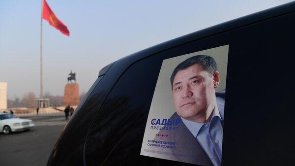 Агитационный плакат кандидата в президенты Кыргызской Республики Садыра Жапарова на стекле автомобиля в Бишкеке