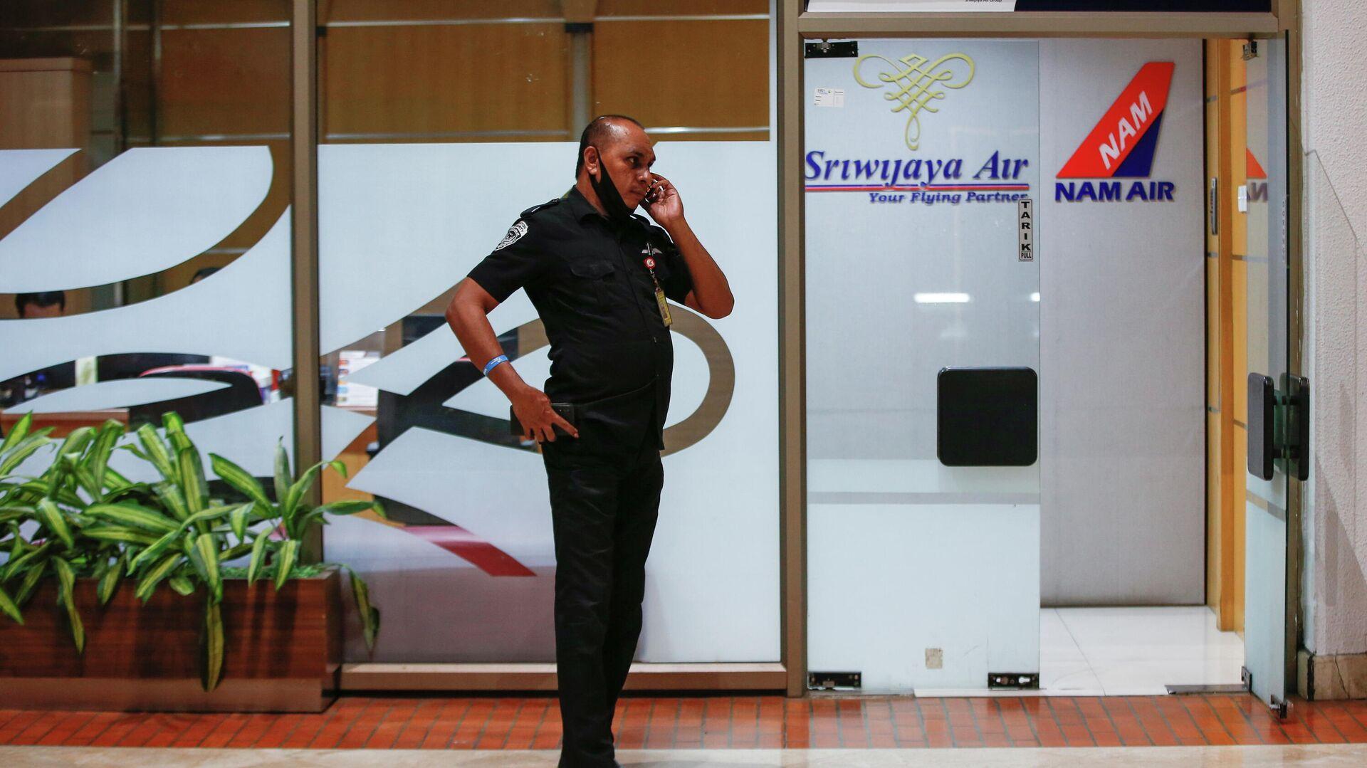 Сотрудник в аэропорту Сукарно-Хатта в Джакарте, после крушения самолета компании Sriwijaya Air - РИА Новости, 1920, 09.01.2021