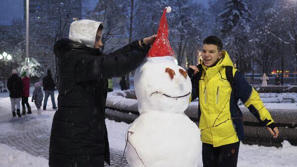 Молодые люди лепят снеговика в сквере им. Жукова в Краснодаре