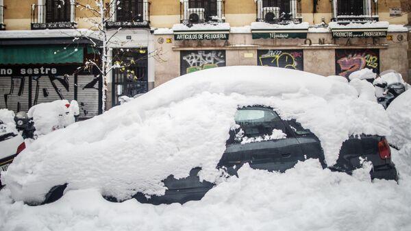 Занесенный снегом автомобиль на одной из улиц в Мадриде
