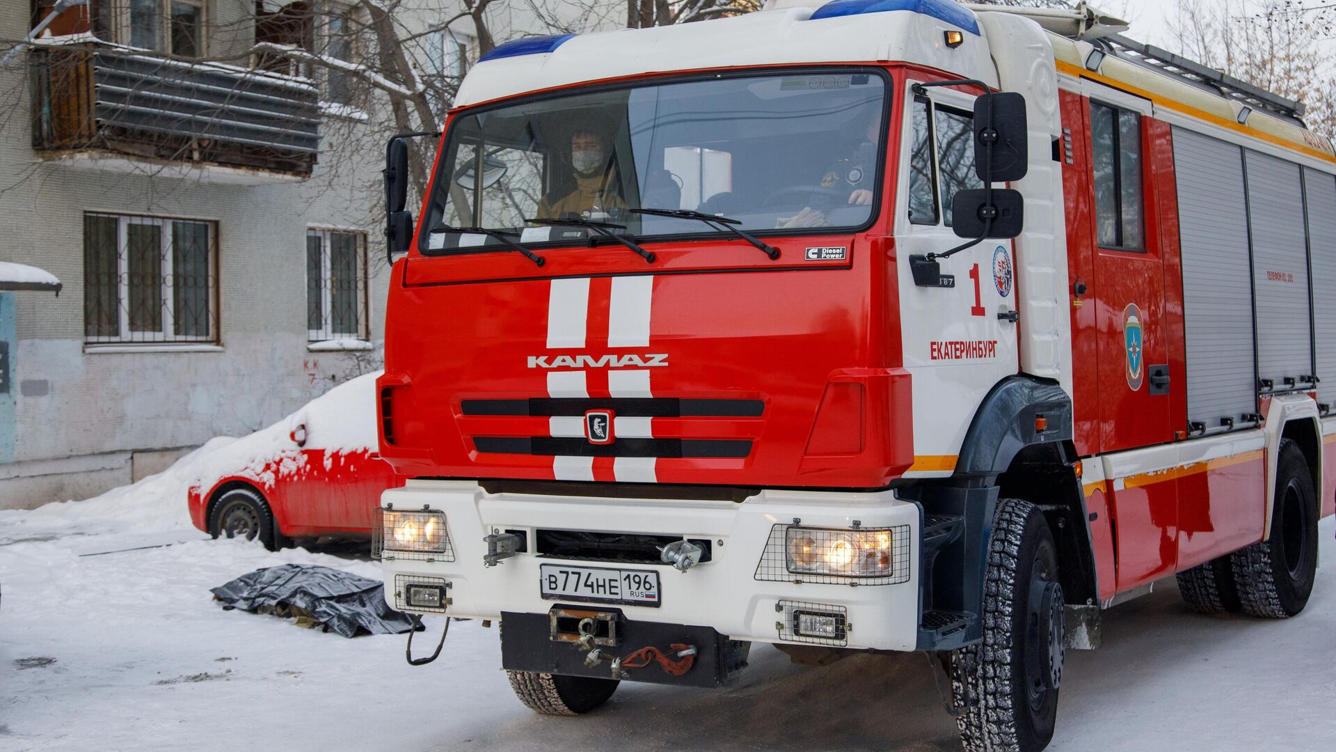 Автомобиль пожарной службы по дворе жилого дома на улице Рассветной в Екатеринбурге, где произошел пожар - РИА Новости, 1920, 01.02.2021