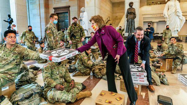 Член палаты представителей США Вики Хартцлер и Майкл Уолтц угощают пиццей военнослужащих Национальной гвардии в здании Капитолия в Вашингтоне