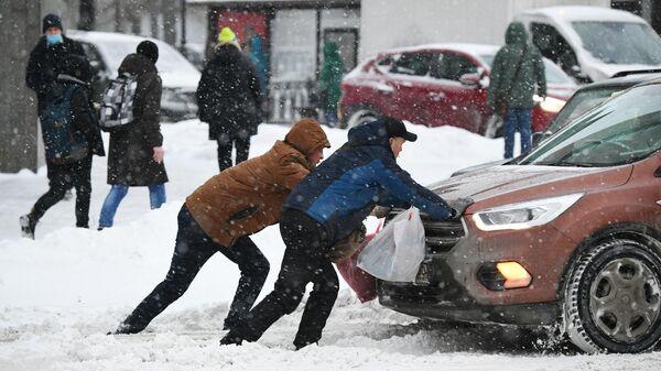 Мужчины толкают машину, застрявшую на дороге во время снегопада