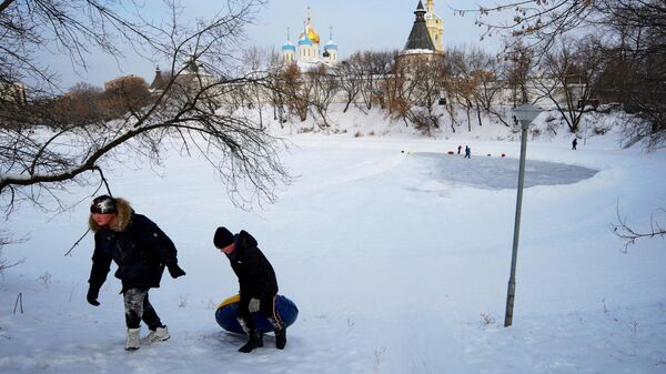Дети катаются на ватрушке возле Новоспасского монастыря в Москве