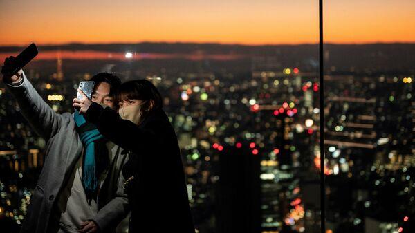 Посетители делают селфи на смотровой площадке Сибуя Скай в Токио