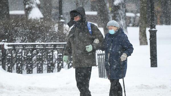 Прохожие идут по Каланчевской улице в Москве во время снегопада
