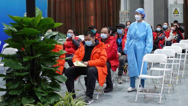Медицинский работник и посетители в центре вакцинации от коронавируса в Пекине