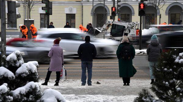 Люди переходят дорогу на одной из улиц в Москве