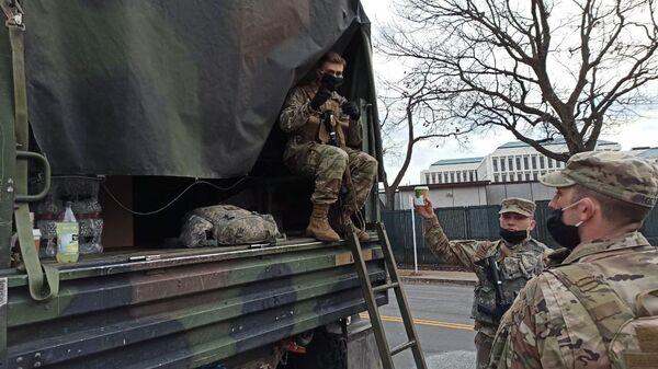 Военнослужащие Национальной гвардии дежурят на одной из улиц неподалеку от здания Капитолия в Вашингтоне