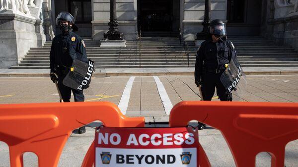Сотрудники полиции дежурят неподалеку от здания Капитолия штата Пенсильвания в Гаррисберге
