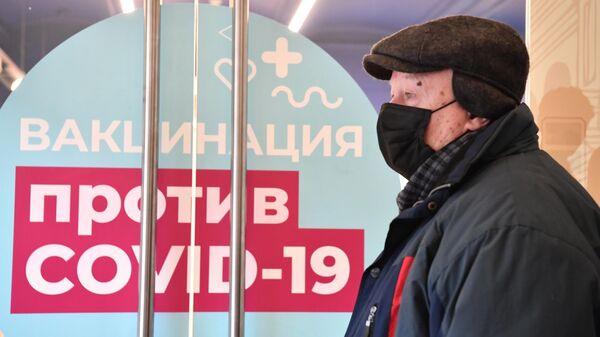 Мужчина возле пункта вакцинации от коронавируса в ГУМе в Москве