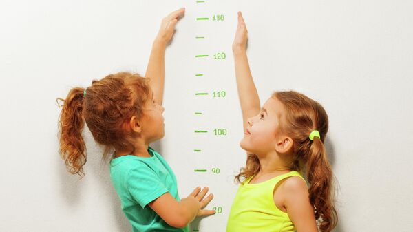 Две девочки измеряют рост