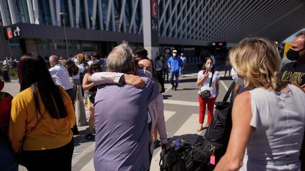 Люди обнимаются при встрече в международный аэропорт Эсейса на окраине Буэнос-Айреса