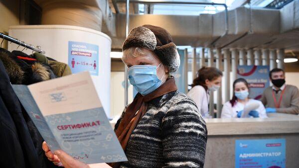 Женщина держит в руках сертификат о вакцинации от СOVID-19 на территории фудмолла Депо.Москва