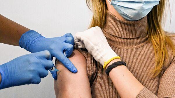 Девушке делают прививку от коронавируса в Геликон-опере в Москве