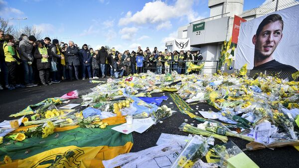 FC Nantes supporters gather in front of a portrait of late Argentinian forward Emiliano Sala to pay tribute prior to the French L1 football match between FC Nantes and Nimes Olympique at the La Beaujoire stadium in Nantes, western France on February 10, 2019. - FC Nantes football club announced on February 8, 2019 that it will freeze the #9 jersey as a tribute to Cardiff City and former Nantes footballer Emiliano Sala who died in a plane crash in the English Channel on January 21, 2019. (Photo by LOIC VENANCE / AFP)