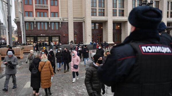 Сотрудник полиции и люди на Манежной площади в Москве во время несанкционированной акции сторонников Алексея Навального