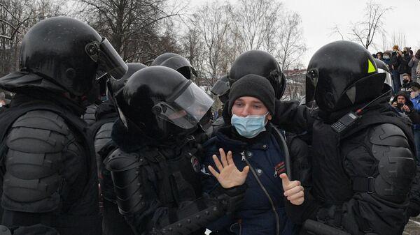 Сотрудники правоохранительных органов задерживают участника несанкционированной акции сторонников Алексея Навального