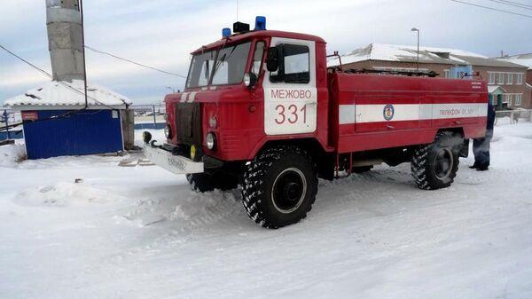 Пожарный автомобиль у водонапорной башни села Межово Красноярского края