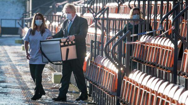 Премьер-министр Великобритании Борис Джонсон несет вакцину от коронавируса AstraZeneca в Лондоне
