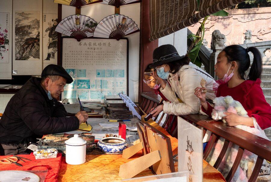 Художник расписывает веер на одной из улиц в Ухани