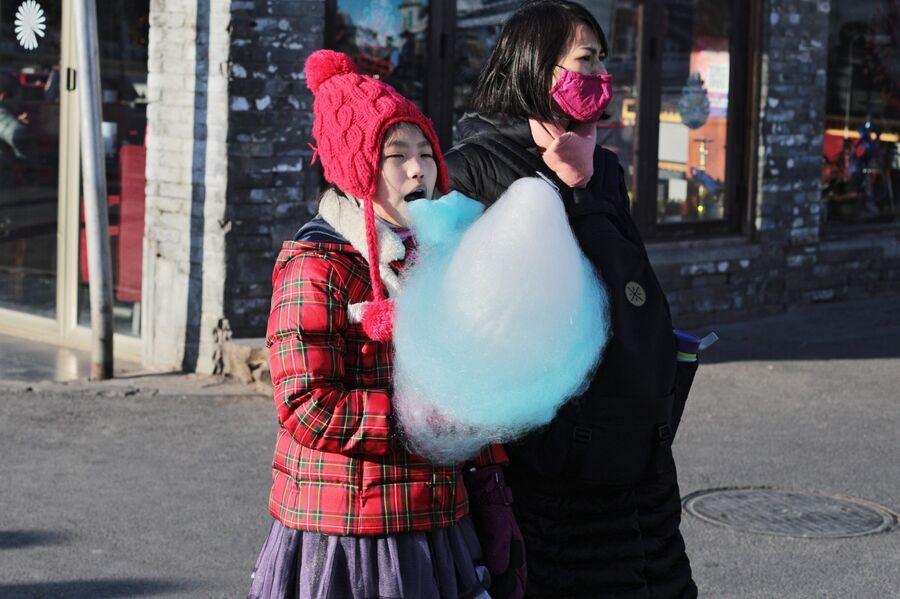 Женщина в защитной маске и девочка с сахарной ватой на улице Пекина