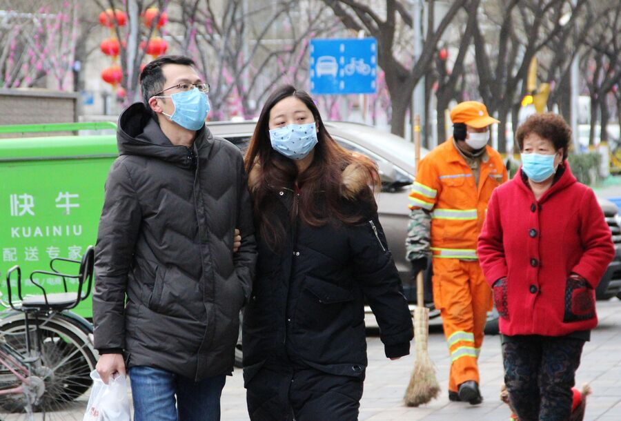 Жители Пекина идут в медицинских масках по улице