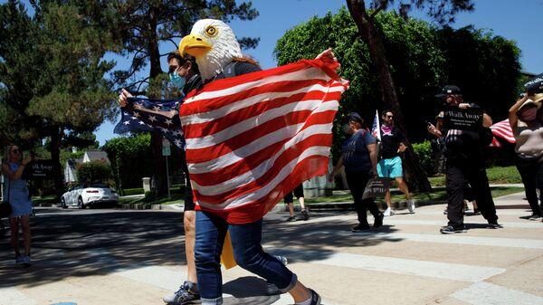 Демонстрант в маске орла с флагом США в Калифорнии